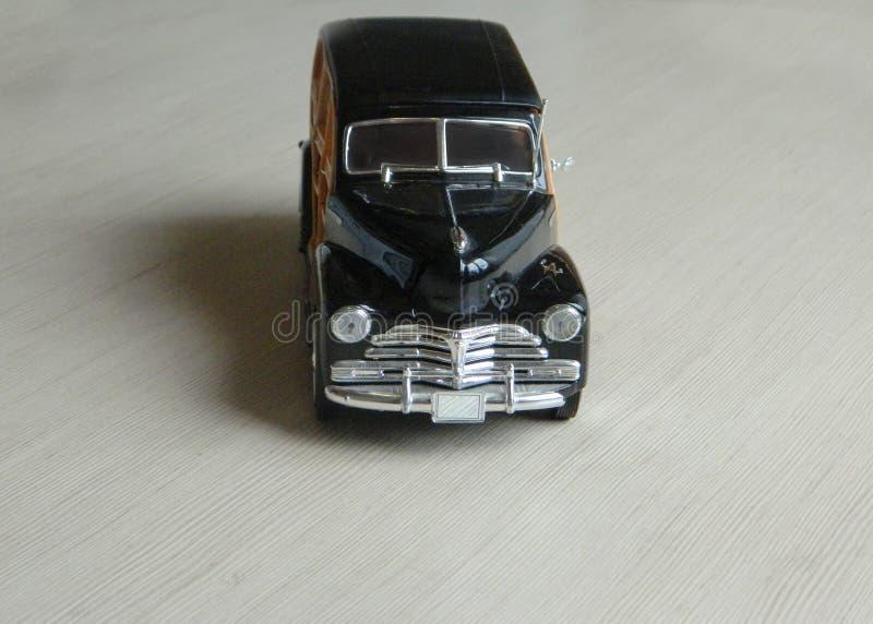Retro- schwarzes Spielzeugauto auf grauer gestreifter Oberfläche Modell des klassischen Weinlesesportwagens mit Schatten und teil stockfotos