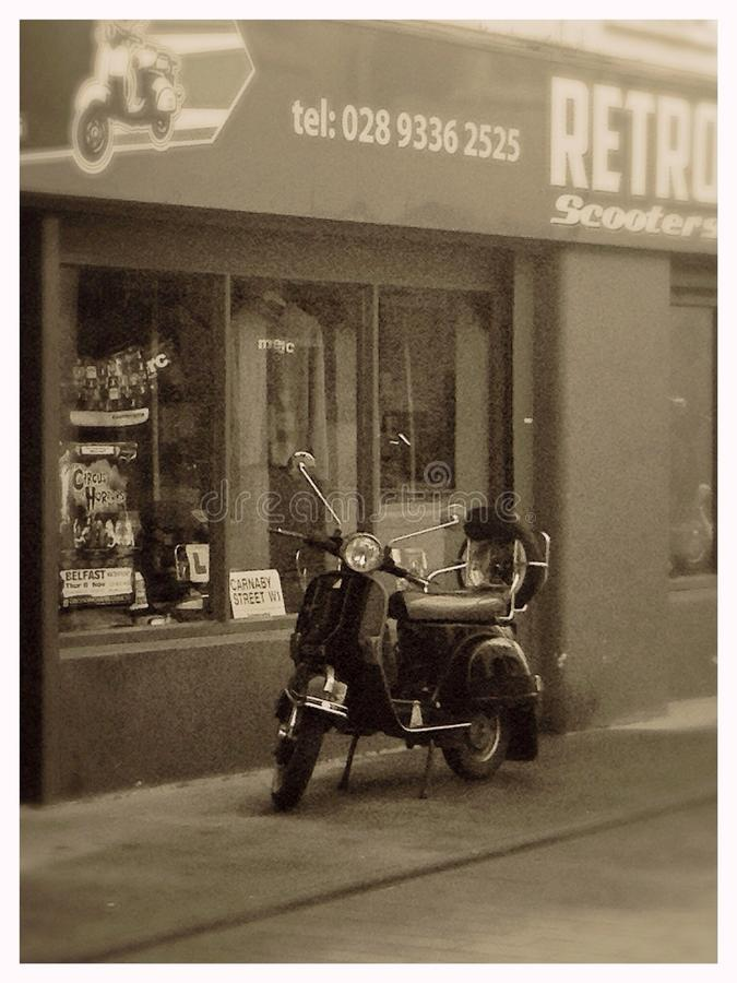 Retro Scooter. Sepia image of a scooter parked outside a scooter dealers shop stock photography