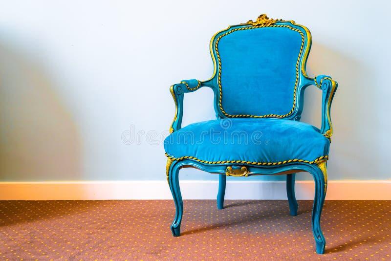 Retro sedia semplice di stile con il tessuto blu e gli ornamenti lussuosi gialli, insieme su una coperta marrone con il modello m fotografia stock libera da diritti