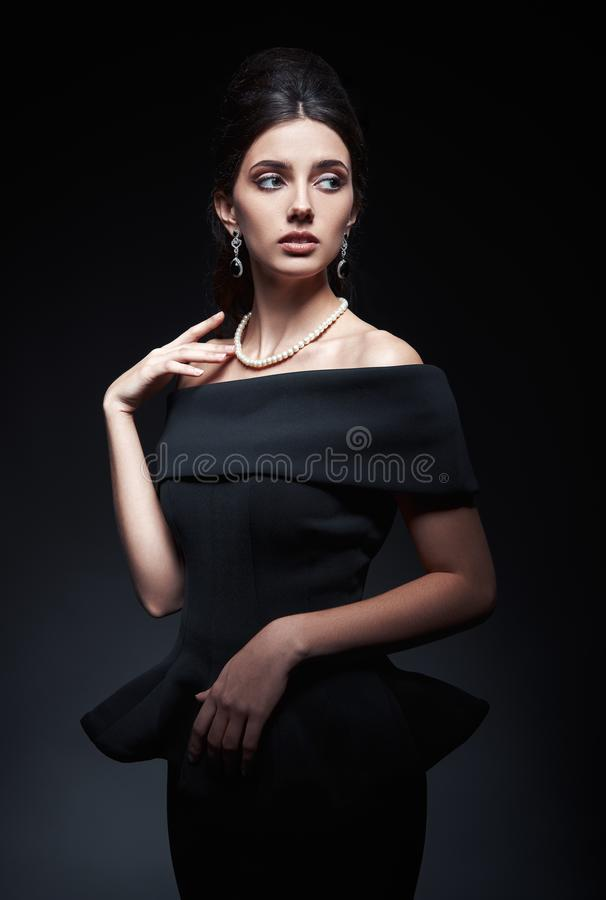Retro shot of beautiful young woman in studio. Vintage portrait of pretty girl in 60s style. Gorgeous lady in black dress and royalty free stock photo