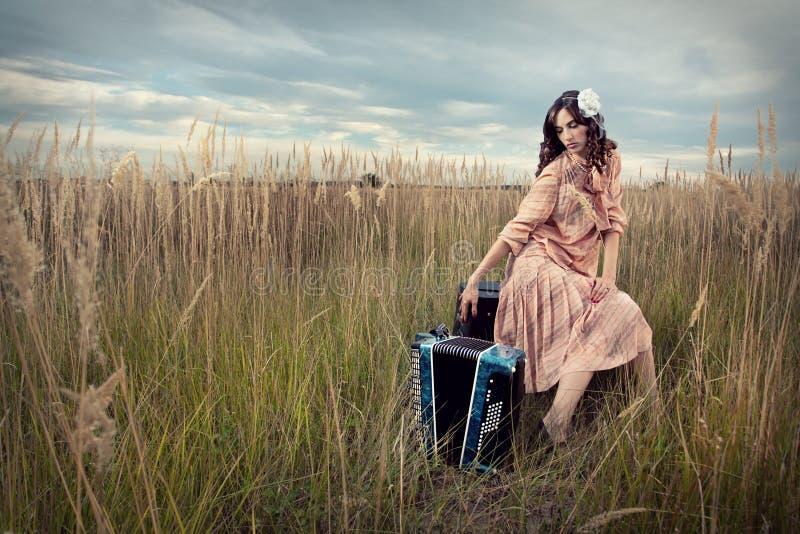 Retro signora nel campo con la fisarmonica fotografie stock libere da diritti