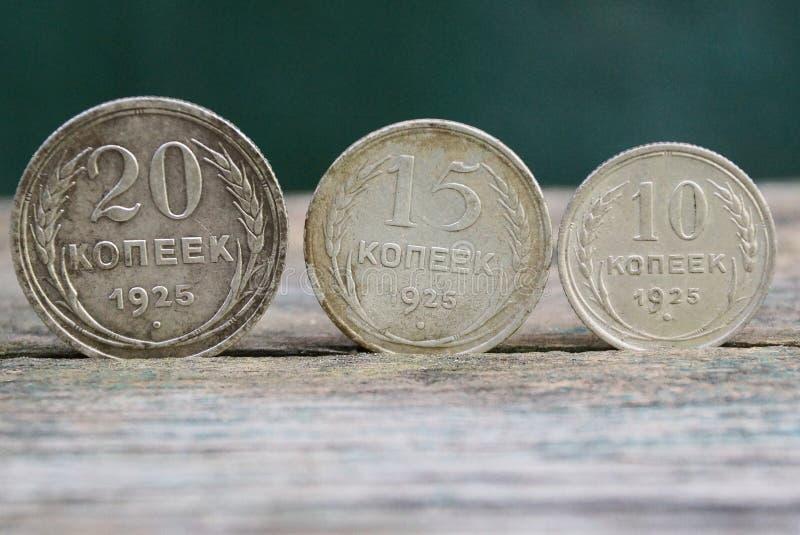 Retro- Silbermünzen stehen auf einer grauen Tabelle stockfotografie