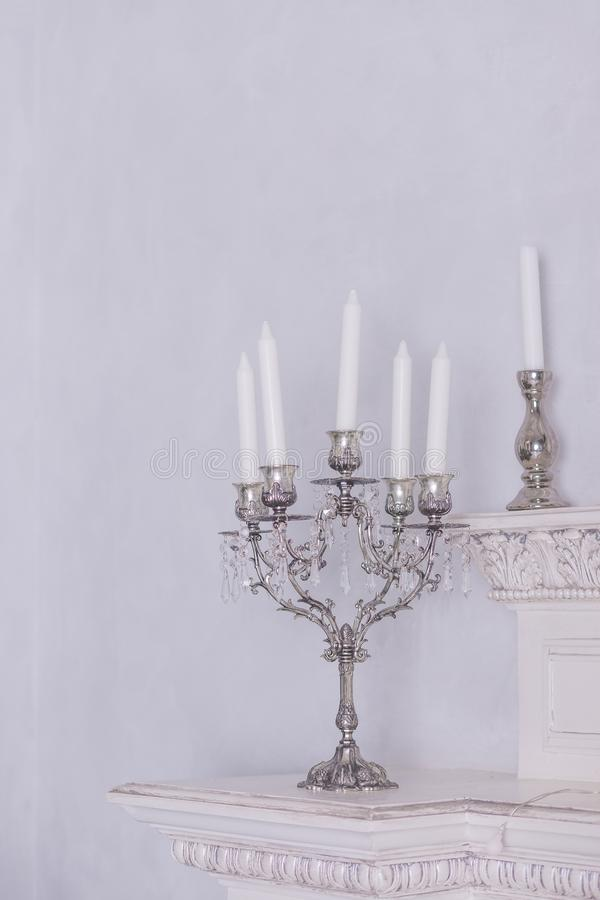 Retro silver candlesticks with white candles, isolated on white wall background. Vertical image.Intererniy light indoor stock photo