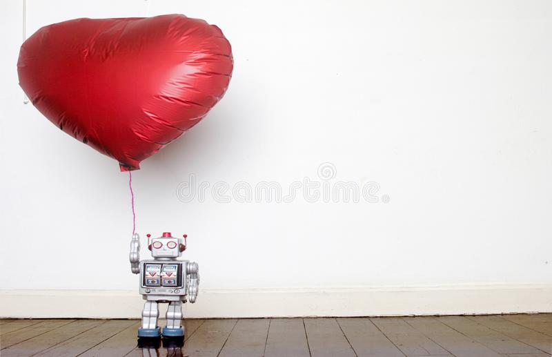Retro silver robot holding a big red balloon standing. On an old wooden floor stock photo