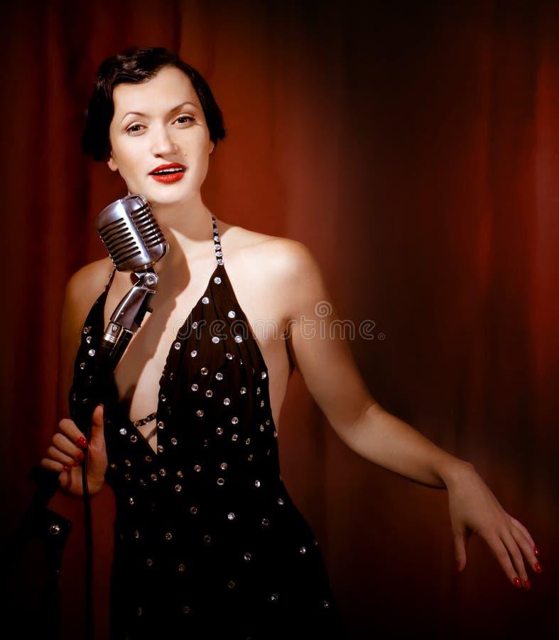 Retro singer sing holding vintage microphone royalty free stock photo