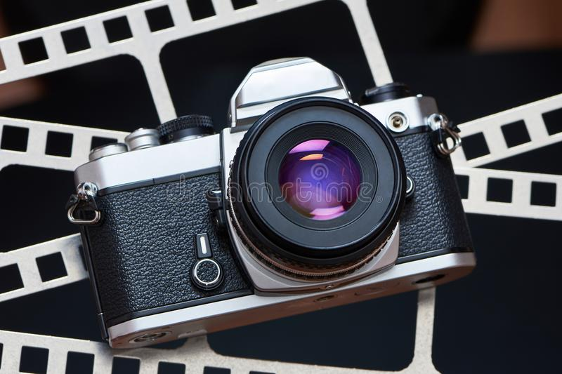 Retro SLR camera on background of perforation film. Retro SLR camera on the background of the perforation of film royalty free stock images