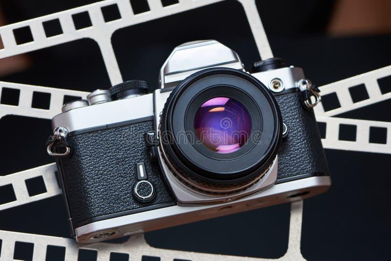 Retro- SLR-Kamera auf Hintergrund des Perforierungsfilmes lizenzfreie stockbilder