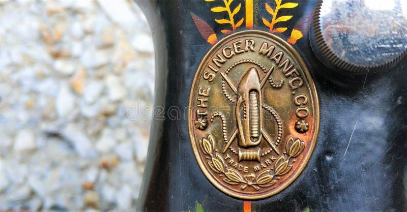Retro slut för gammal symaskintappning upp Sångare Factory Emblem royaltyfri fotografi