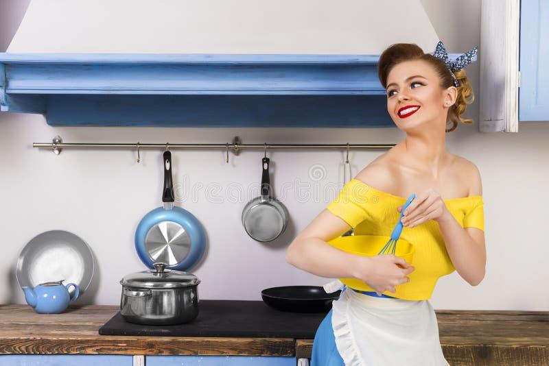 Retro speld op meisjeshuisvrouw in de keuken stock foto