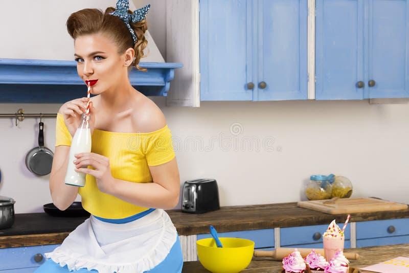 Retro speld op meisjeshuisvrouw in de keuken stock foto's