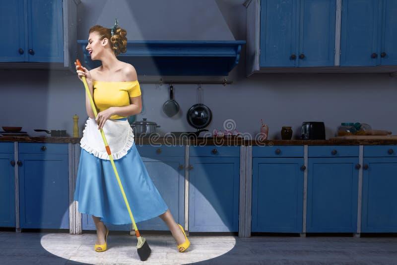 Retro speld op van de de holdingszwabber van de meisjeshuisvrouw de zingende en schoonmakende vloer stock foto's