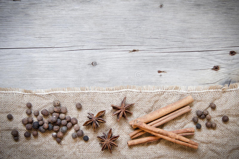 Retro spices background. Cinnamon, pepper and anice on burlap and wood stock photos