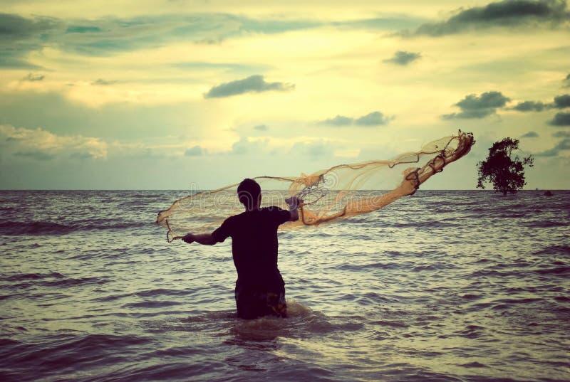Retro spojrzenie wizerunek mężczyzna miotania sieć rybacka obrazy stock