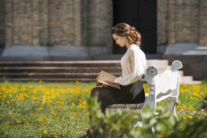 Retro stående av en härlig drömlik flicka som utomhus läser en bok Mjuk tappningtoning arkivfoto