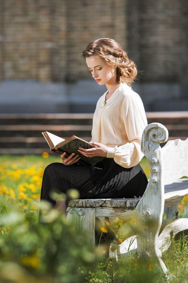 Retro stående av en härlig drömlik flicka som utomhus läser en bok Mjuk tappningtoning royaltyfria bilder
