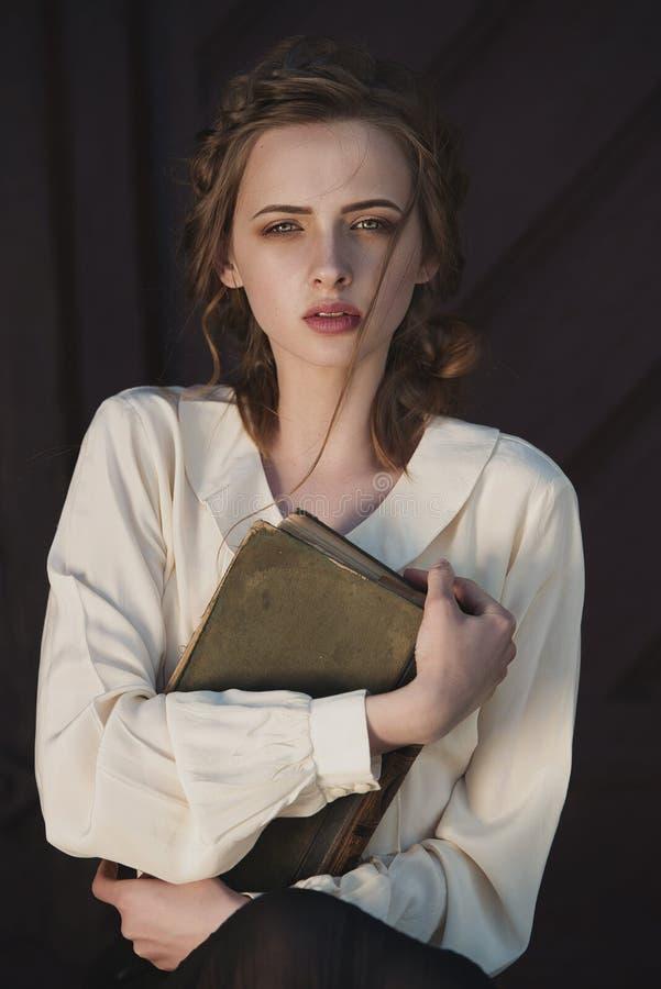 Retro stående av en härlig drömlik flicka som utomhus rymmer en bok i händer Mjuk tappningtoning arkivfoto