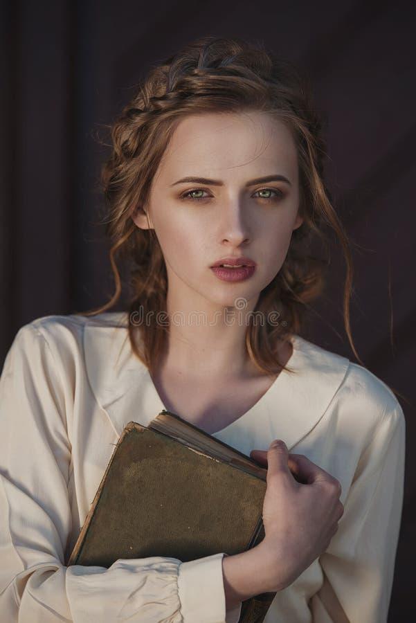 Retro stående av en härlig drömlik flicka som utomhus rymmer en bok i händer Mjuk tappningtoning royaltyfri bild