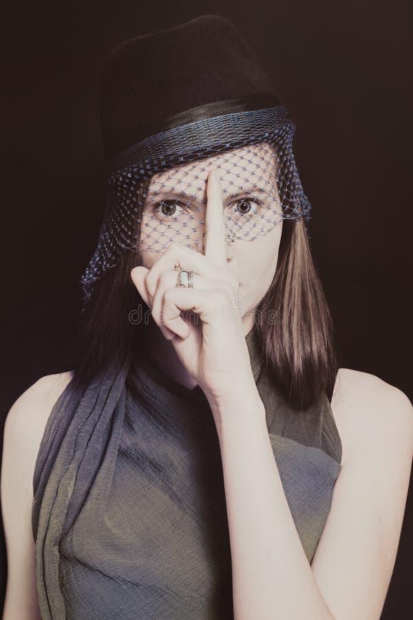 Retro stående av en härlig ung kvinna i en hatt med en skyla royaltyfri bild