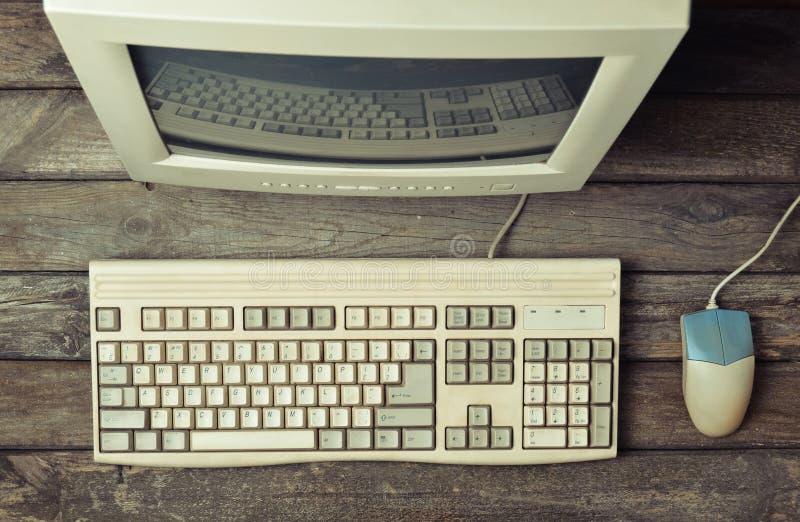 Retro stationär dator på ett lantligt träskrivbord, tappningworkspace royaltyfri foto