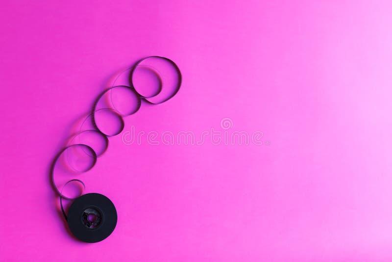 Retro stijlfilm voor oude videocamera op al roze document backgound, vat creatief concept samen Retro jaren '80 met exemplaarruim stock afbeeldingen