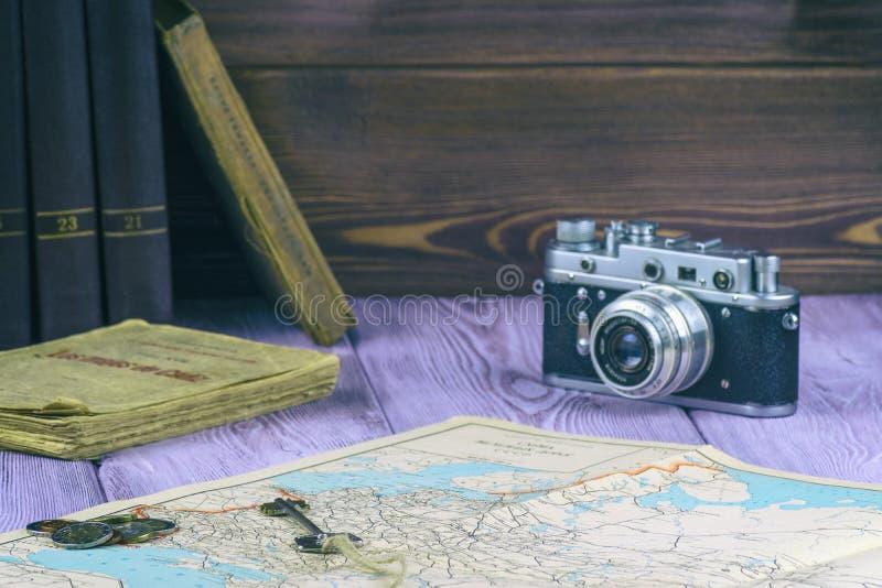 Retro-stil Gamla böcker och en översikt på tabellen Mynt för filmkamera och för en handfull royaltyfri foto