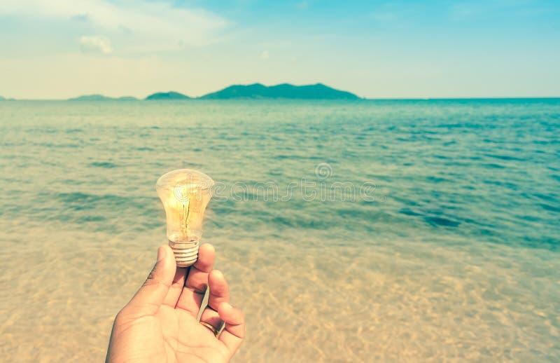 Retro stile della lampadina della tenuta dell'uomo sulla spiaggia con la montagna fotografia stock