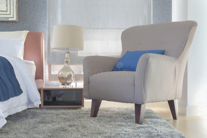 Retro stilfåtölj med kudden bredvid säng i modernt sovrum royaltyfria foton