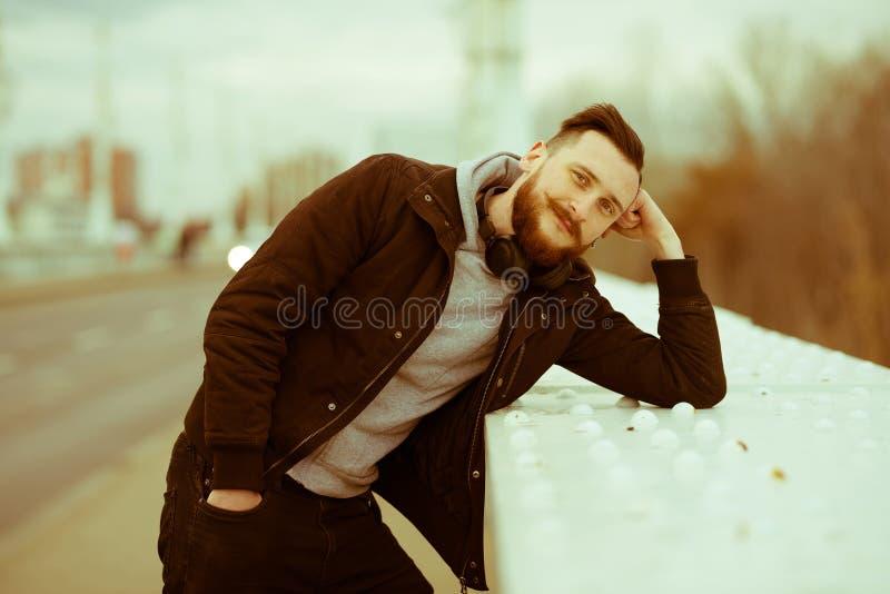Retro stilfoto av en hipsterman som tänker på en bro royaltyfri bild