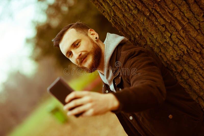 Retro stilfoto av en hipsterman som tar en selfie i parkera arkivfoton