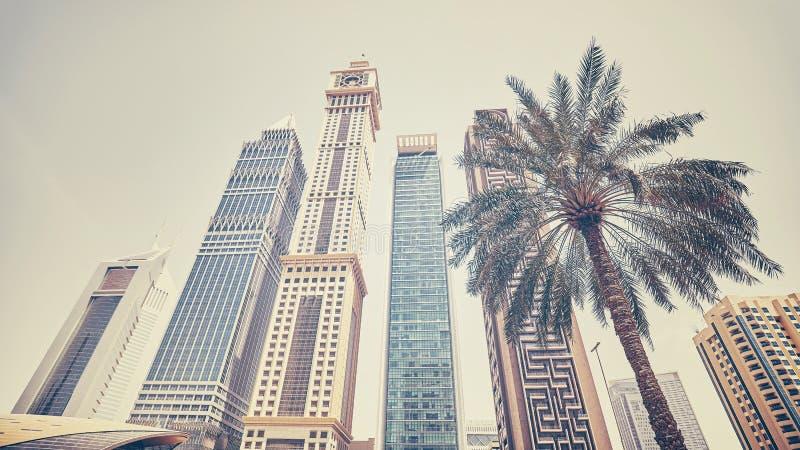 Retro- stilisiertes panoramisches Foto von Dubai-Wolkenkratzern mit einer Palme lizenzfreie stockfotos