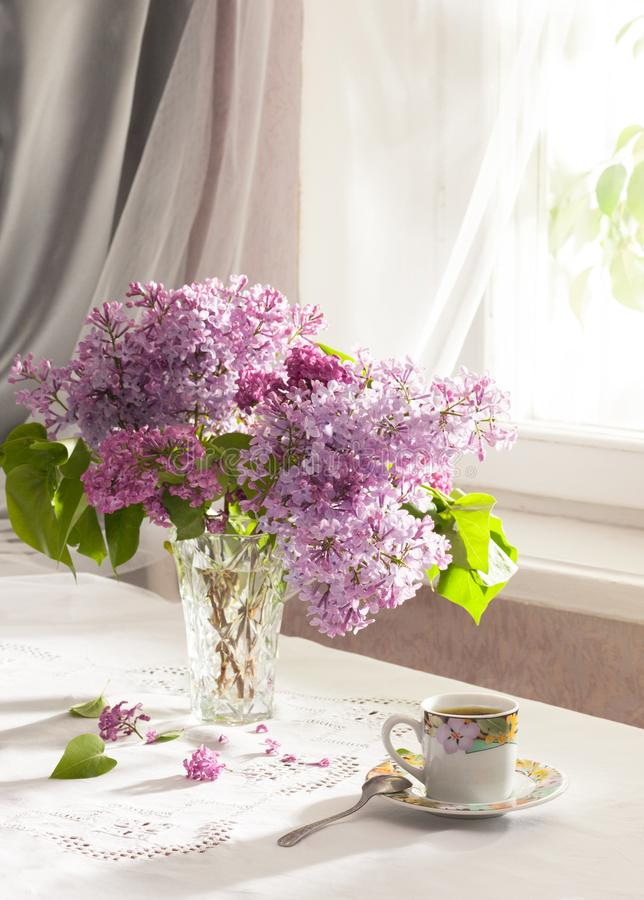 Retro still life with a bouquet of lilac and cup of coffee. Soft focus stock photography