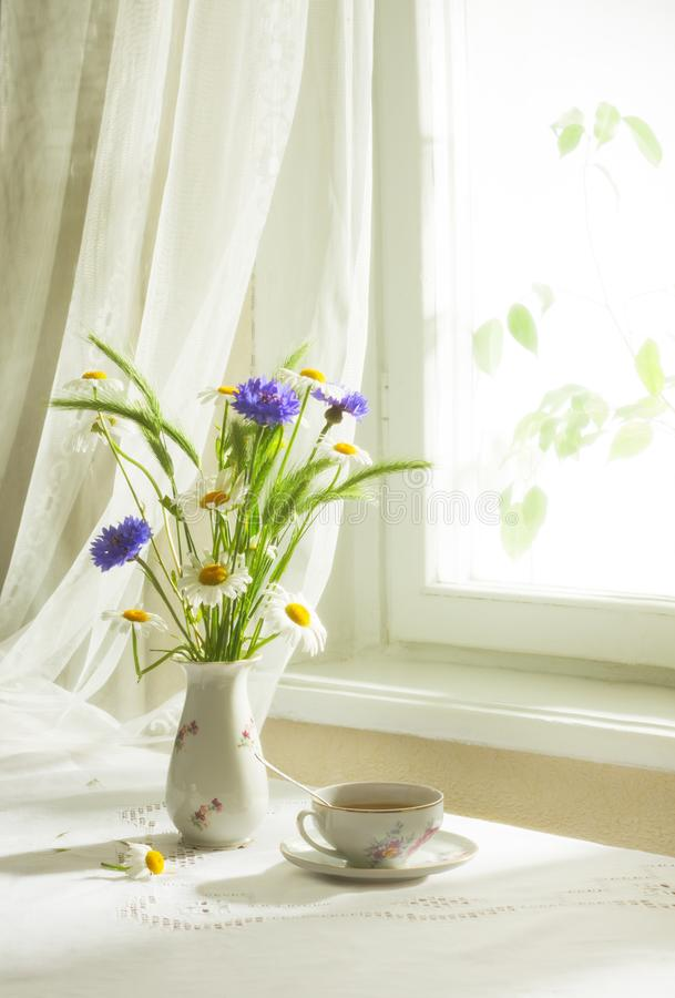 Retro still life with a bouquet of wildflowers and cup of tea. Soft focus royalty free stock photos