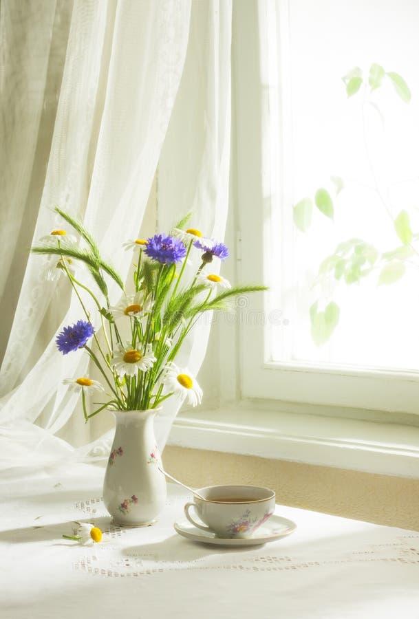 Retro stilleven met een boeket van wildflowers en kop thee Zachte nadruk royalty-vrije stock foto's