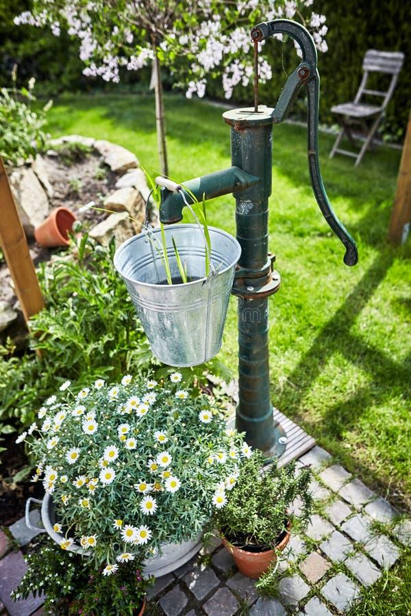 Retro stilträdgård som landskap med den gamla vattenpumpen fotografering för bildbyråer