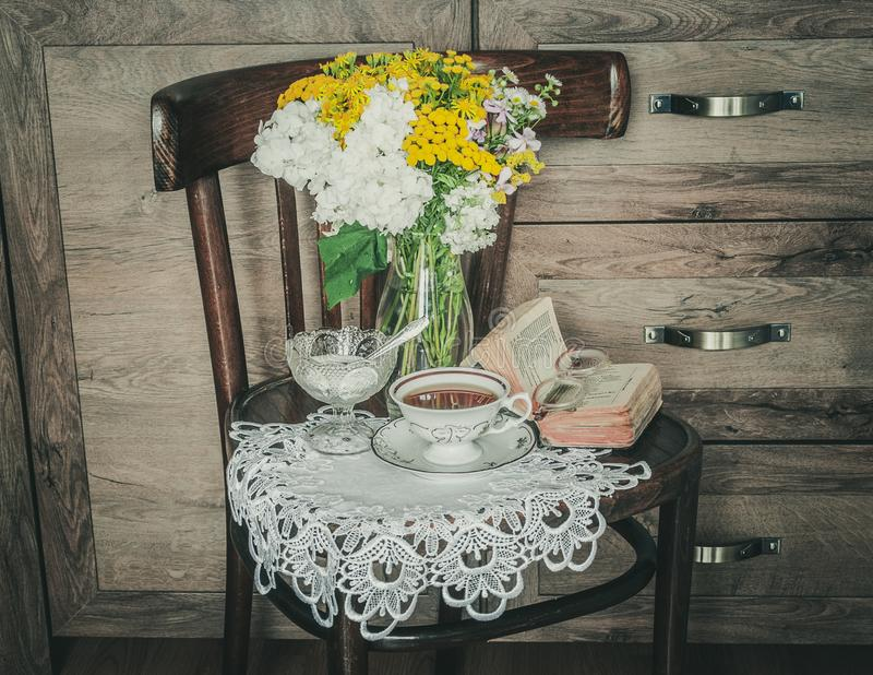 Retro stol med blommor i en vas, en gammal bönbok och en kopp te royaltyfria foton
