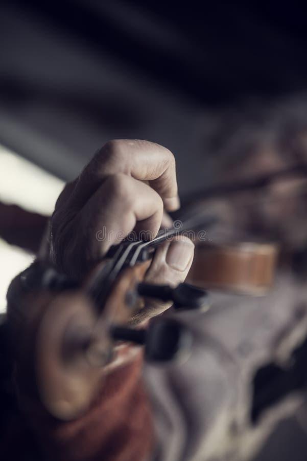Retro stonowany wizerunek mężczyzna z brudnymi gwoździami bawić się skrzypce obrazy stock