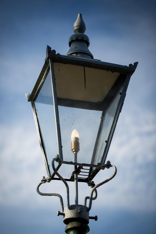 Retro street lamp shining against cloudy sky background royalty free stock photos
