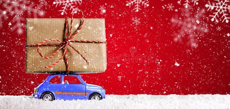Retro stuk speelgoed auto met Kerstmisgiften stock afbeelding