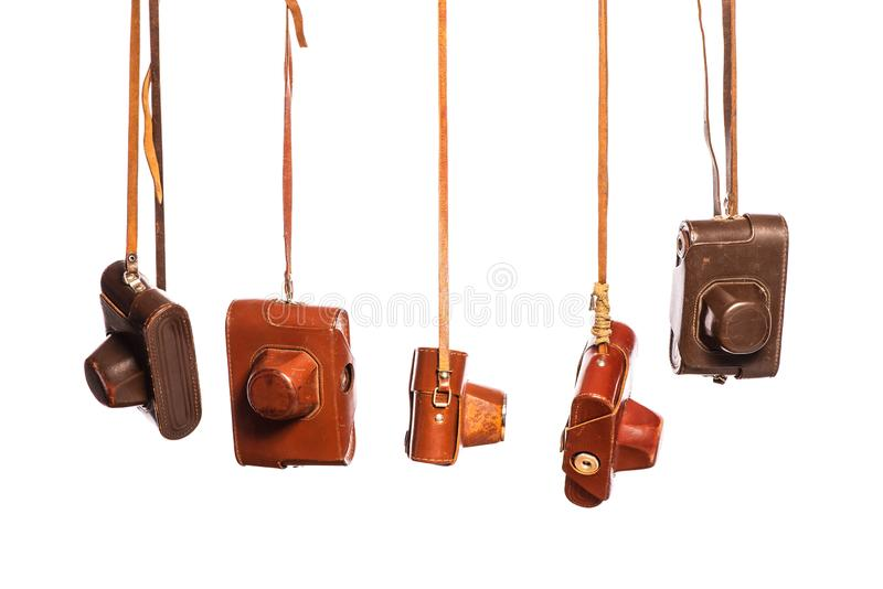Retro-style analog cameras in leather covers, isolated on white background with clipping path. Collectibles of antiques. Design elements stock image