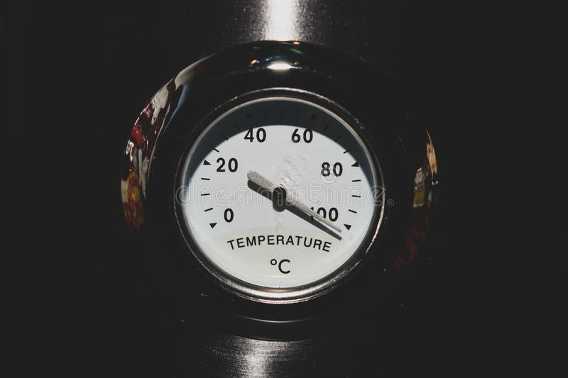 Old style analog thermometer on the metal background. high temperature concept stock photography
