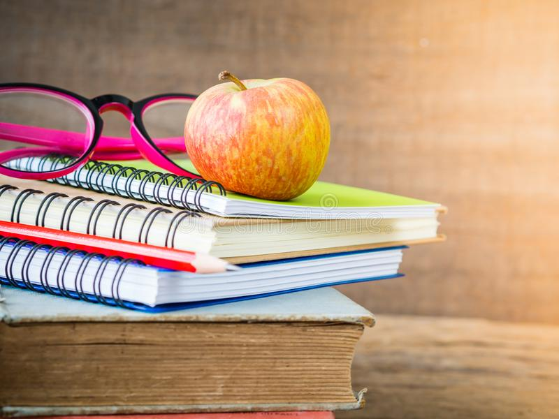 Retro style of apple on stacks of books with pink glasses and red pencil on wooden table background. Back to school concept. Retro style of apple on stacks of royalty free stock photos