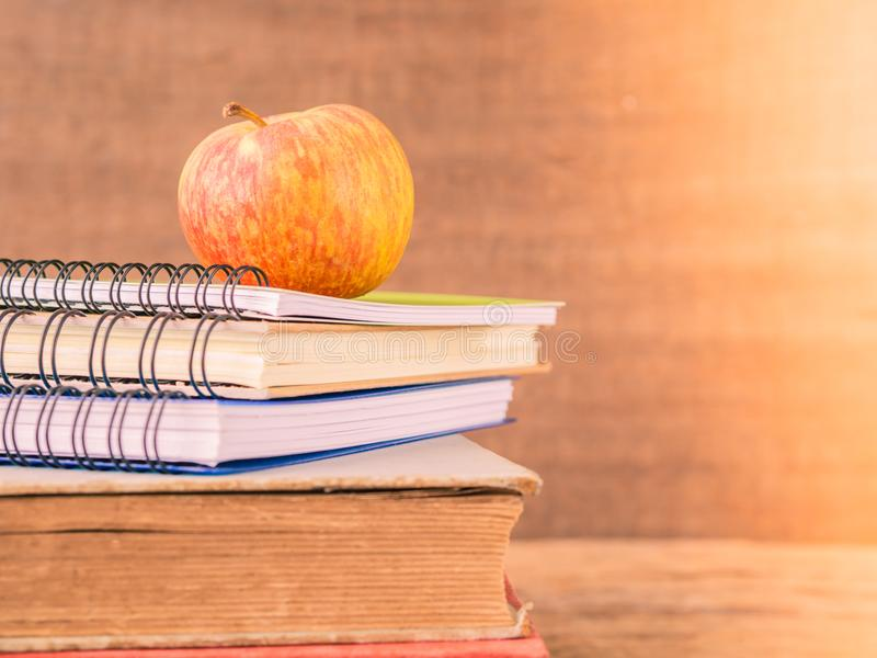 Retro style of apple on stacks of books on wooden table background. Back to school concept. Retro style of apple on stacks of books on wooden table background royalty free stock images