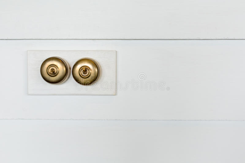 Retro style brass power switches. On white wall stock images