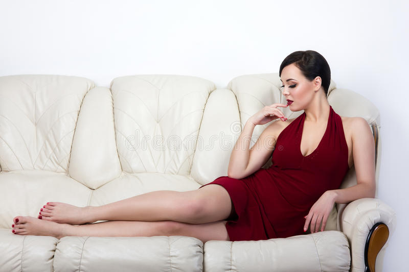 Retro style brunette woman lying on sofa royalty free stock photography