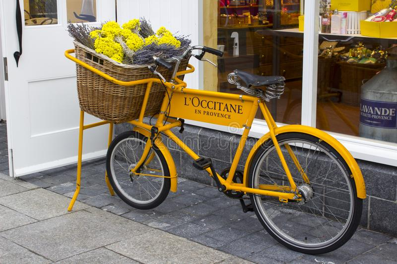 A retro style butcher`s bicycle with advertisements on display outside the L`Occitane shop in Ireland`s up market Kildare Villag. 16 March 2018 Retro style royalty free stock photography