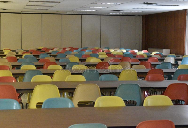 Retro table and chairs in a cafeteria in a school. A retro style cafeteria with wood paneling chairs tables blue yellow pink linoleum floor school vintage old stock image