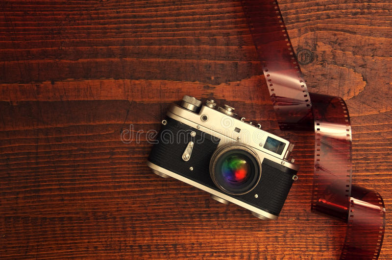 Retro style camera. On a wooden table plate with some 35 overexposed film strip royalty free stock image