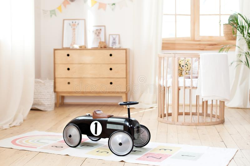 Retro style children`s racing car in a children room. Black vintage model of race car for boy. Great car for a charming playground royalty free stock photo