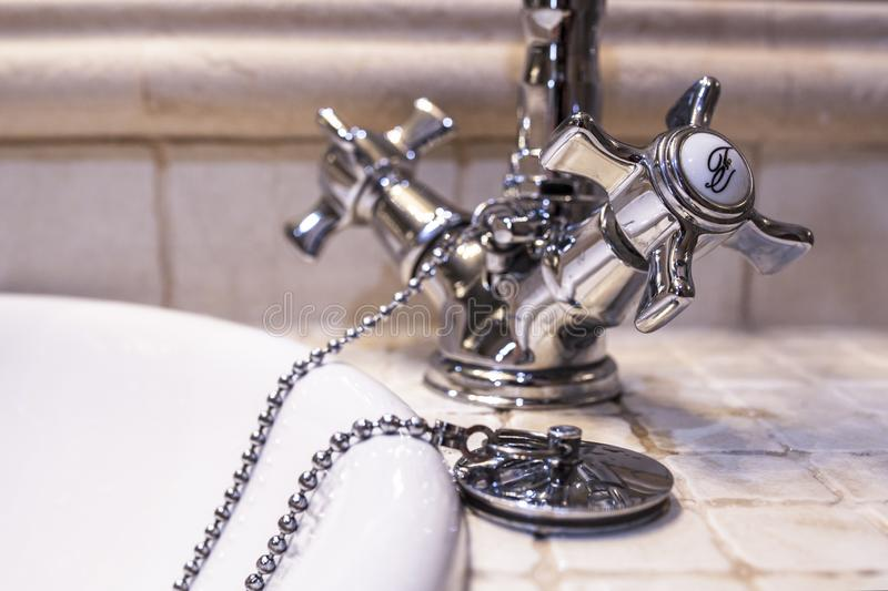 Retro style chrome basin faucet. Plug with chain stock images