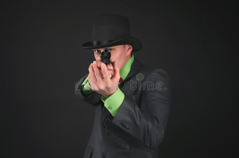 Spy. Retro style detective agent with gun and bowler hat on his head is aiming forwards isolated on the black background royalty free stock image